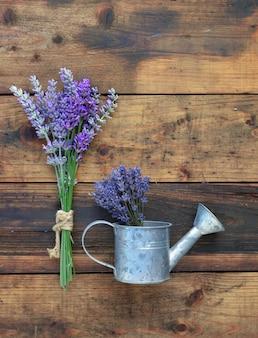 Mazzo di fiori di lavanda e poco annaffiatoio su fondo di legno rustico