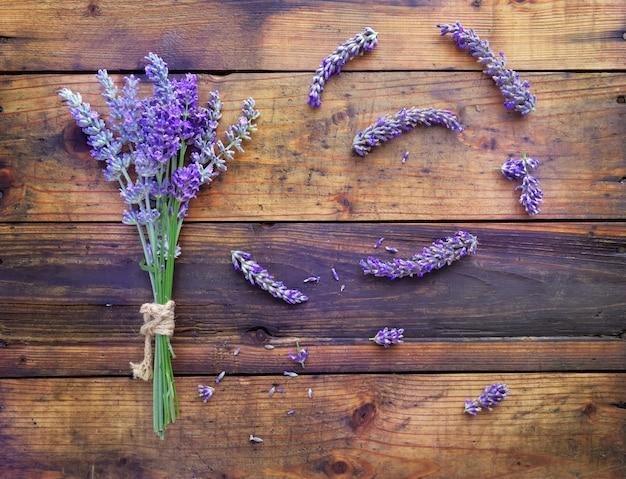 Mazzo di fiori e petali di lavanda su fondo di legno rustico
