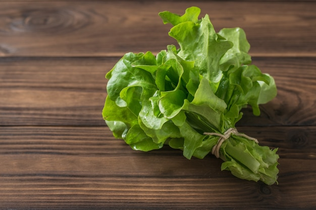 Mazzo di lattuga legato con una corda su un tavolo di legno. il concetto di mangiare sano.