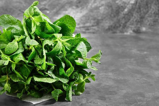 Mazzo di menta, menta verde, menta piperita legati con spago su uno sfondo grigio