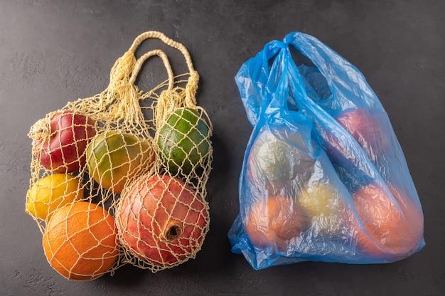Mazzo di frutta, verdura e verdure organiche miste in un sacchetto di stringa e plastica su sfondo scuro.