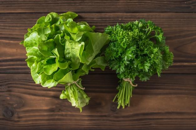 Un mazzetto di prezzemolo e un mazzetto di lattuga su un tavolo di legno. il concetto di mangiare sano. lay piatto.