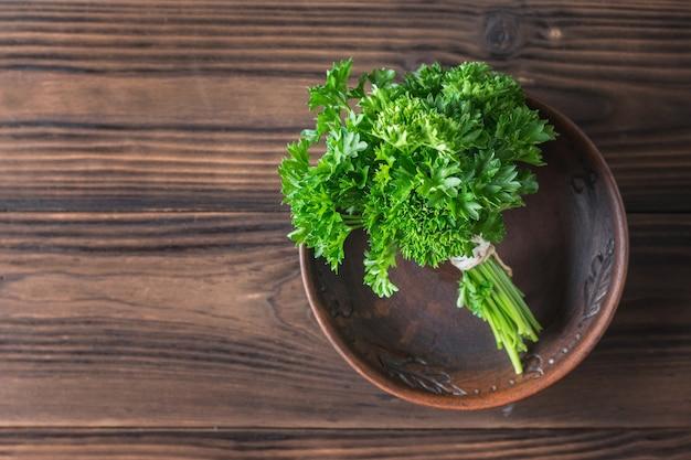 Mazzo di prezzemolo in una ciotola di argilla su un tavolo di legno. il concetto di mangiare sano. lay piatto.