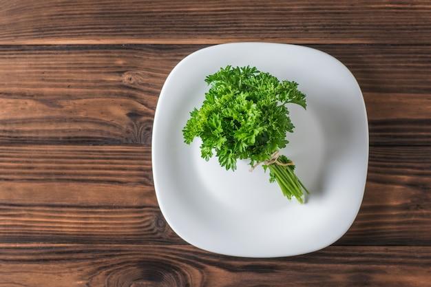 Mazzo di prezzemolo su un piatto bianco su un tavolo di legno. il concetto di mangiare sano. lay piatto.