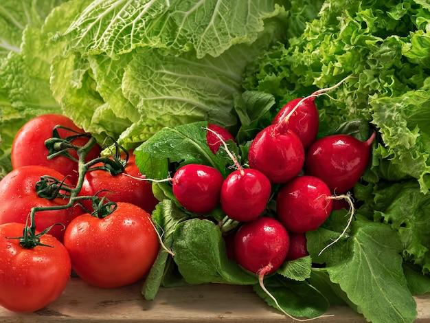 Un mazzo di ravanelli, un mazzo di pomodori maturi. cavolo cinese ed insalata freschi. gocce d'acqua sulle verdure. avvicinamento.
