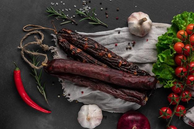 Mazzo di salsicce fatte in casa secche rosse su una superficie scura, aglio e tela di sacco, vista dall'alto