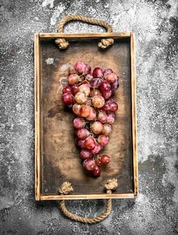 Grappolo d'uva rossa su un vassoio di legno. su fondo rustico.
