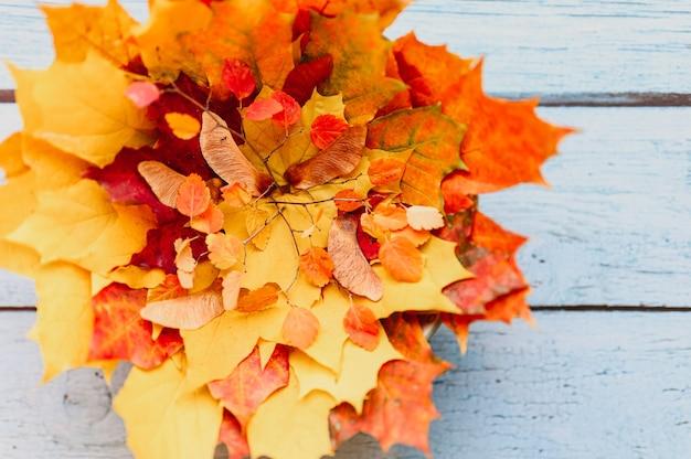 Un mucchio di foglie di acero autunnali secche rosse e gialle e ramoscelli autunnali su uno sfondo di legno blu