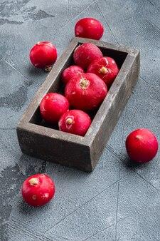 Mazzo di ravanelli maturi impostato, in una scatola di legno, sul tavolo grigio