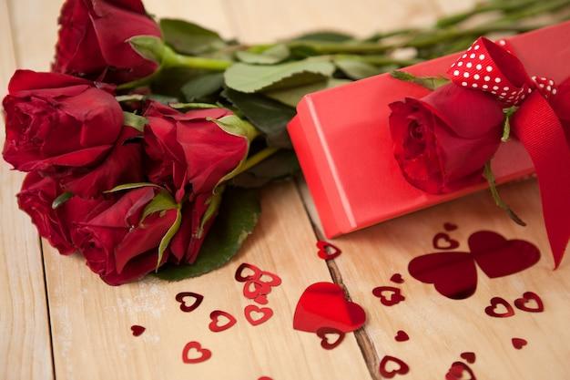 Mazzo di rose e confezione regalo circondato da decorazioni a cuore