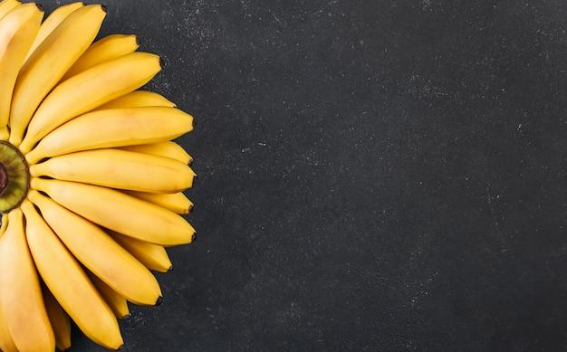 Un mazzo di piccole banane mature su uno spazio ruvido grigio scuro copia spazio