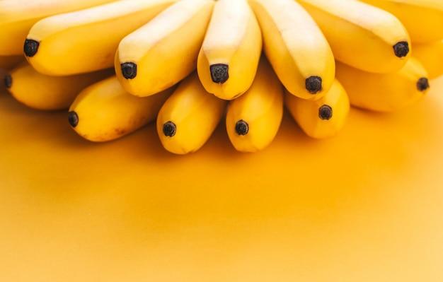 Un mazzo di piccole banane mature su uno sfondo giallo copia spazio