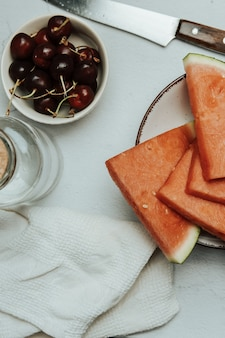 Mazzo di frutta estiva e fresca su un tavolo bianco minimalista, anguria e ciliegia, concetti di benessere e cibo sano, gustoso, strutturato, copia spazio