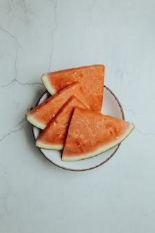 Mazzo di frutta estiva e fresca su un tavolo bianco minimalista, anguria, benessere e concetti di cibo sano, gustoso, strutturato, copia spazio