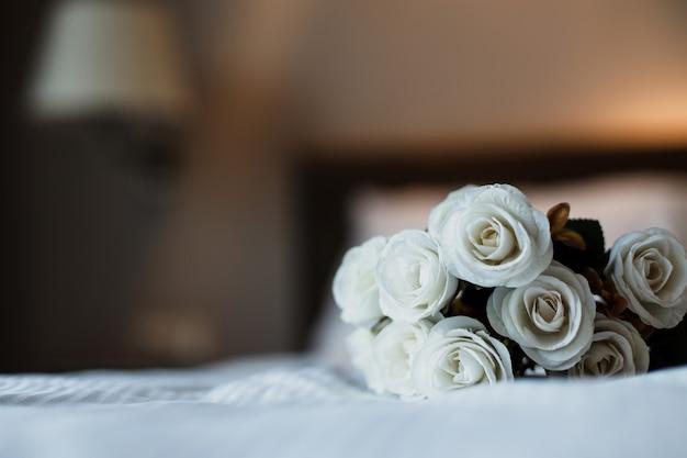 Un mazzo di fiori di rosa bianca sul letto per una celebrazione romantica