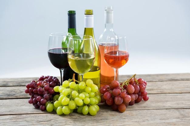 Grappoli d'uva vari con bicchiere di vino e bottiglie sulla tavola di legno