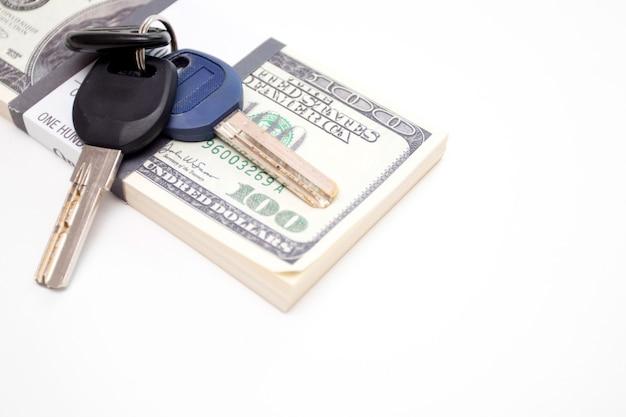 Pacco di dollari e chiave su sfondo bianco.
