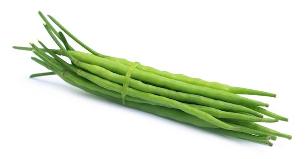 Fascio di fagioli di senape verde su sfondo bianco