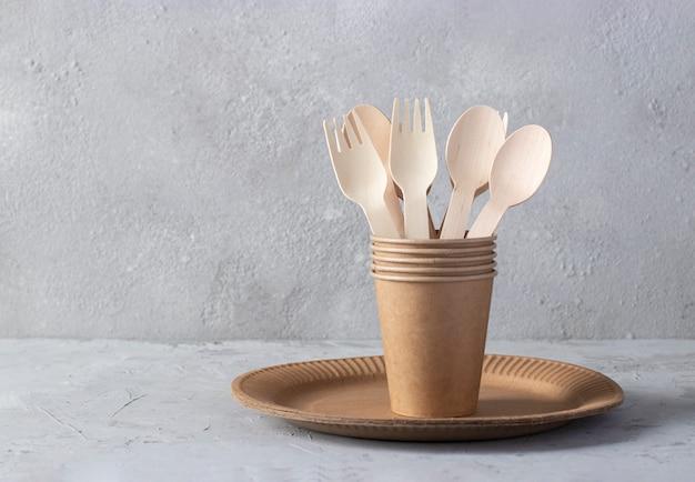 Bunner eco friendly utensili da cucina usa e getta su sfondo grigio. forchette e cucchiai di legno in bicchiere di carta su piatto di carta. zero rifiuti concetto con spazio per il testo.