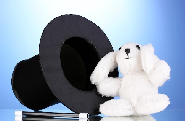 Coniglietto e cilindro nero su sfondo blu