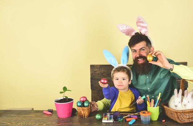 Orecchie da coniglio e orecchie da coniglio disegnano padre e figlio che dipingono le uova di pasqua