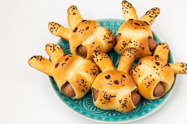 Panini a forma di lepri con salsicce si trovano su un piatto blu su sfondo bianco, idea culinaria per bambini, vista dall'alto