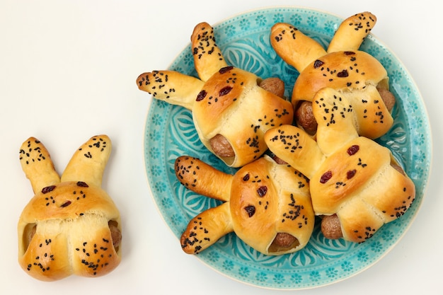 I panini a forma di lepri con salsicce si trovano su un piatto blu su una superficie bianca, idea culinaria per bambini, vista dall'alto