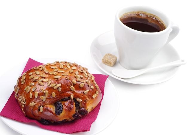 Panini uvetta e semi di girasole con caffè su sfondo bianco