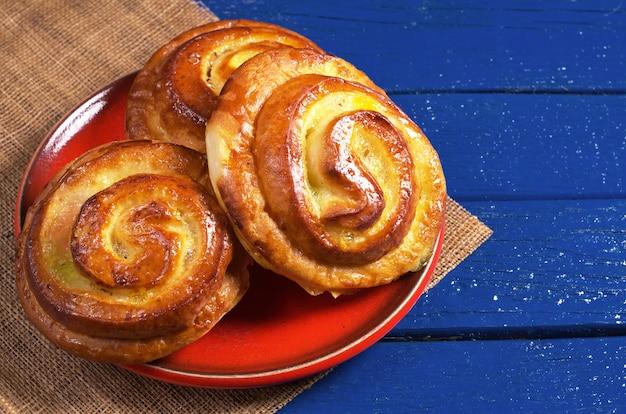 Panini con marmellata di albicocche in piatto rosso su fondo di legno blu