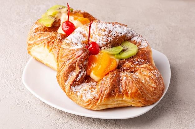 I panini con la frutta si trovano su un primo piano bianco del piatto