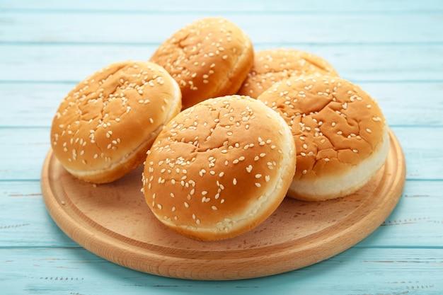 Panini per hamburger sul tagliere su un fondo di legno blu. vista dall'alto.
