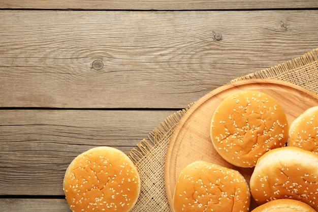 Panini per hamburger sul tagliere su un fondo di legno grigio. vista dall'alto.