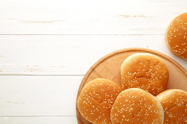 Panini per hamburger sul tagliere su un fondo di legno bianco. vista dall'alto.
