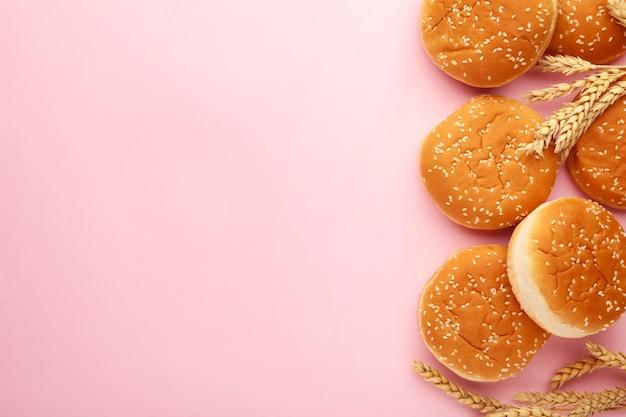 I panini hamburger con spighetta su uno sfondo rosa. vista dall'alto.