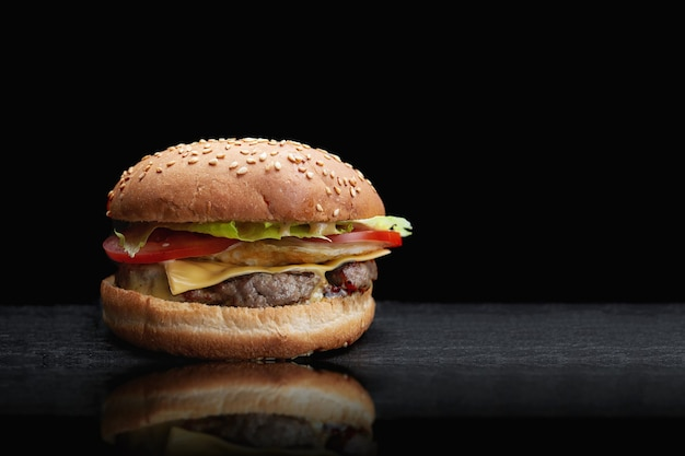Hamburger, cheeseburger, con cotoletta di carne, formaggio, lattuga e pomodoro, su sfondo nero, con riflessione e posto per il testo