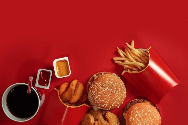 Hamburger e patatine hamburger e patatine fritte in scatola di carta rossa fast food su sfondo rosso