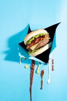 Hamburger che esce da una carta blu con salse gocciolanti.