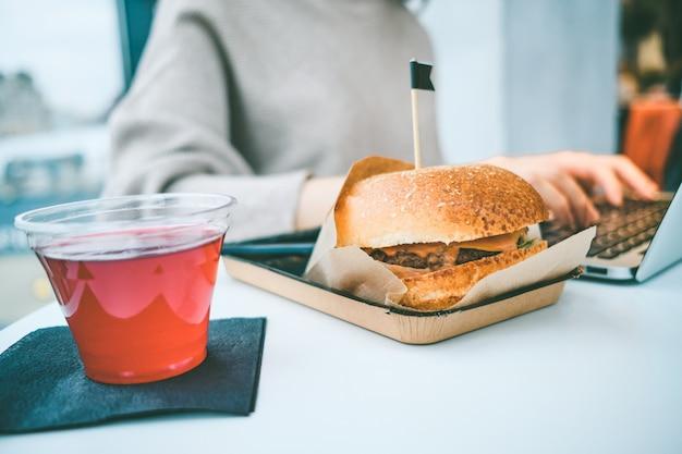 Hamburger in carta artigianale sul tavolo accanto al succo e la ragazza lavora a un computer portatile.