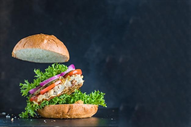Hamburger delizioso panino con cotoletta alla griglia e verdure porzione
