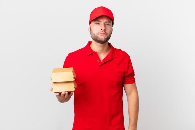 Hamburger consegnare l'uomo triste e piagnucoloso con uno sguardo infelice e piangere
