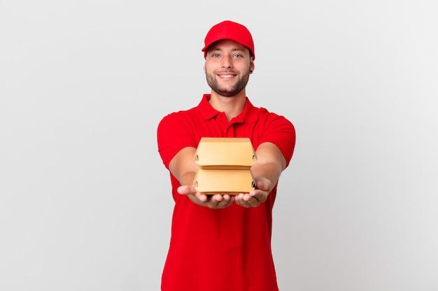 L'hamburger consegna l'uomo sorridente felicemente con amichevole e offrendo e mostrando un concetto