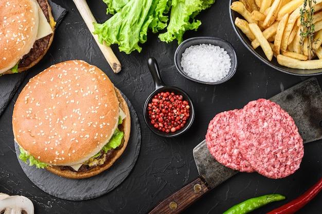 Hamburger e ingredienti freschi su sfondo nero, piatto laici.