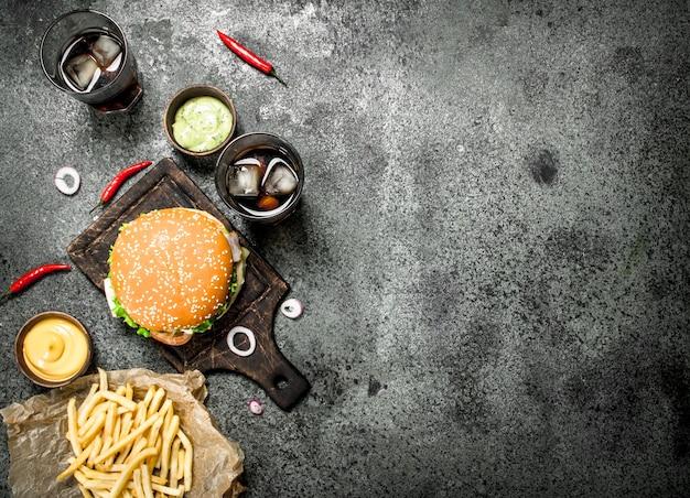 Hamburger di manzo fresco con cola e patatine fritte. su fondo rustico.