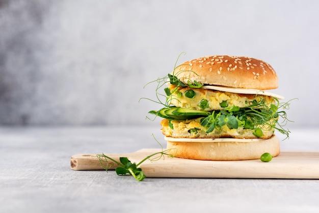 Hamburger vegetariano sano con uova e germogli di piselli e semi microgreen, insalata fresca, fetta di cetriolo su una tavola di legno da taglio su sfondo chiaro. messa a fuoco selettiva