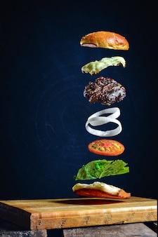 Hamburger isolato con ingredienti in aria che galleggia nella parete blu scuro in un tavolo di legno