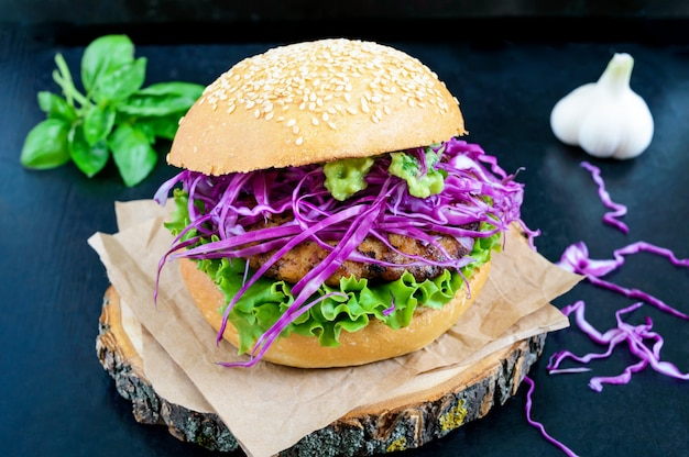 Hamburger - cotoletta succosa con insalata di cavolo rosso, salsa di avocado con aglio su un panino croccante sul nero