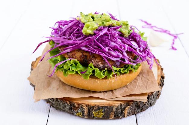 Hamburger - cotoletta succosa con insalata di cavolo rosso, salsa di avocado con aglio su un panino croccante su un tavolo di legno bianco.