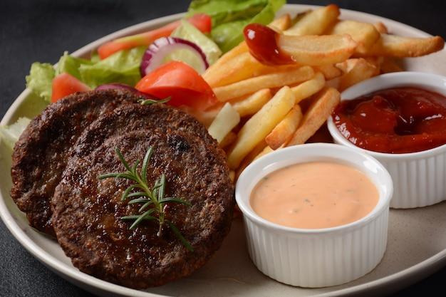 Bistecche di carne di hamburger patatine fritte e insalata su sfondo nero