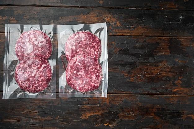 Hamburger di carne sigillato sottovuoto pronto per il set da cucina sous vide, su un vecchio tavolo di legno scuro