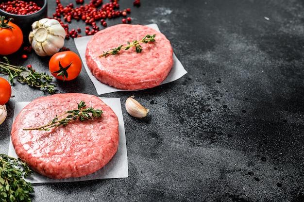 Polpette di hamburger, terra fresca cruda, tritare la carne sul nero. vista dall'alto. copia spazio